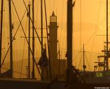 Chania lighthouse and ship masts at sunset